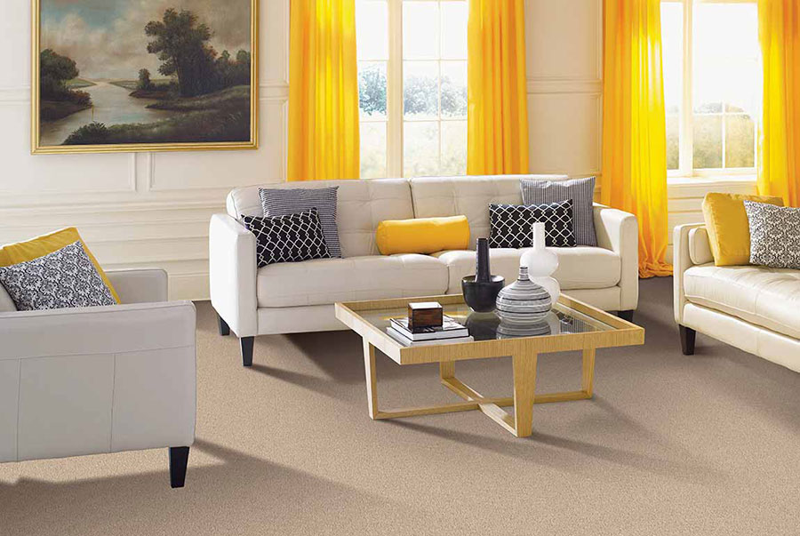 Living room with white couches on tan carpet accented by yellow curtains and throw pillows.